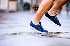 Stäng sig upp av ben av den oigenkännliga löparen, staden, pöl royaltyfri fotografi