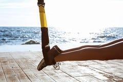Stäng sig upp av ben i trx, över havsbakgrund royaltyfri fotografi
