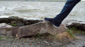 Stäng sig upp av benet av bärande jeans för en man som står på en vagga i floden Gymnastikskor som kliver på en sten Slut upp av  fotografering för bildbyråer