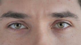 Stäng sig upp av blinkaögon av den unga mannen som ser kameran lager videofilmer