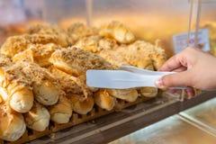 Stäng sig upp av bröd för floss för handplockninggriskött med klämman arkivfoton