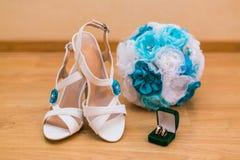 Stäng sig upp av bröllopbukett och bruds skor och guld- cirklar Arkivfoton