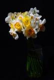 Stäng sig upp av bukett av vit och gulna påskliljor i en vas på D royaltyfria bilder