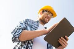 Stäng sig upp av byggmästare i hardhat med minnestavlaPC fotografering för bildbyråer