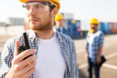 Stäng sig upp av byggmästare i hardhat med walkietalkien arkivbild