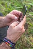 Stäng sig upp av caucasian man med regnbågearmband som smsar på hans mobiltelefon arkivfoton