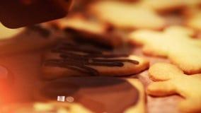 Stäng sig upp av chokladduggregn över nya bakade julkakor arkivfilmer