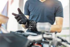 Stäng sig upp av cyklisten som sätter på svarta handskar och sitter på motorcykeln royaltyfria bilder