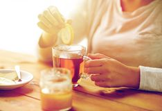 Stäng sig upp av dåligt kvinnan som dricker te med citronen Royaltyfria Foton