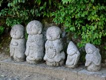 Stäng sig upp av de lilla Nagomi Jizo statyerna som lokaliseras utanför den Arashiyama bambuskogen, Kyoto royaltyfri foto