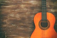 Stäng sig upp av den akustiska gitarren mot en träbakgrund royaltyfri foto