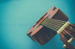 Stäng sig upp av den akustiska gitarren mot en träbakgrund royaltyfri bild