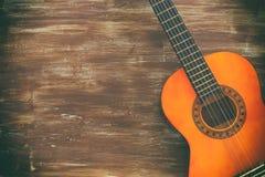 Stäng sig upp av den akustiska gitarren mot en träbakgrund Arkivbild
