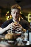 Stäng sig upp av den attraktiva mannen som äter den stora smakliga hamburgaren royaltyfri foto