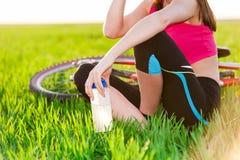 Stäng sig upp av den attraktiva unga aktiva kvinna och cykeln Arkivfoton