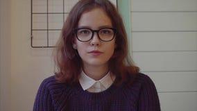 Stäng sig upp av den attraktiva unga tonårs- flickan som ler på kameran stock video