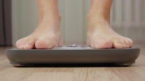 Stäng sig upp av den barfota mannen som väger på skalan, främre sikt på ben stock video