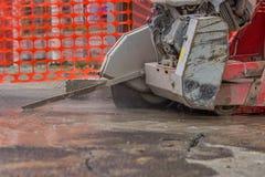 Stäng sig upp av den bitande asfaltvägen med diamantsågbladet Fotografering för Bildbyråer