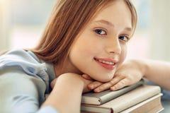 Stäng sig upp av den charmiga flickan som vilar hakan på böcker Royaltyfria Foton