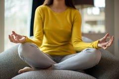 Stäng sig upp av den fridsamma kvinnan som mediterar att sitta i stol hemma royaltyfria foton