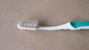 Stäng sig upp av den gamla använda tandborsten på brunt papper Arkivfoton