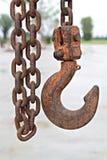 Stäng sig upp av den gamla rostiga metallkedja och kroken på konstruktionsplatsen Royaltyfria Bilder