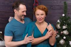 Stäng sig upp av den gladlynta mannen som kramar hans fru nära julgranen royaltyfri fotografi
