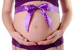 Stäng sig upp av den gravida buken som dekoreras med bandet Royaltyfria Bilder