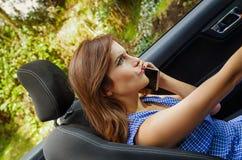 Stäng sig upp av den härliga caucasian kvinnan som inom använder hennes mobiltelefon av den svarta bilen, medan hon kör i ett sud arkivfoto