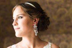 Stäng sig upp av den härliga kvinnan som bär skinande diamantörhängen arkivfoto