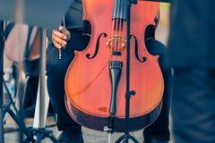 Stäng sig upp av den hållande violoncellen för den manliga cellisten på en utomhus- konsert arkivbilder