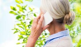 Stäng sig upp av den höga kvinnan som kallar på smartphonen arkivbilder