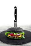 Stäng sig upp av den hemlagade svarta hamburgaren med ost Ostburgare med den svarta bullen på vit träbakgrund Royaltyfria Foton