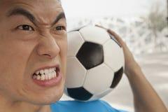 Stäng sig upp av den ilskna unga mannen som rymmer en fotbollboll på hans skuldra royaltyfria foton