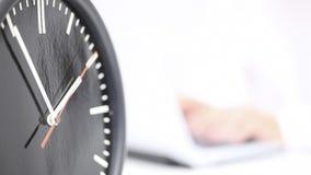Stäng sig upp av den körande klockan med affärsmannen som arbetar på bärbara datorn i baksidan