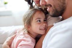 Stäng sig upp av den lyckliga familjen i säng hemma Arkivfoto
