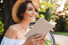 Stäng sig upp av den lyckliga unga flickan som läser en bok arkivbild
