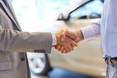 Stäng sig upp av den manliga handskakningen i auto show eller salong Arkivfoton