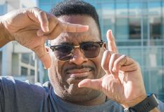 Stäng sig upp av den middlle åldrades svarta mannen med fingrar som inramar framsidan fotografering för bildbyråer