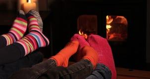 Stäng sig upp av den mysiga familjen hemma som bär sockor som värme fot vid flammor stock video