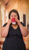Stäng sig upp av den nätta feta kvinnan i en härlig klänning, den dra koppen av coffe i en suddig bakgrund royaltyfria foton