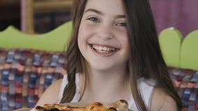 Stäng sig upp av den nätta unga flickan som tycker om lukten av en pizza långsamt arkivfilmer