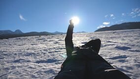 Stäng sig upp av den oigenkännliga mannen som ligger på snö och ser den glänsande solen till och med hans fingrar på solig dag Ha arkivfilmer