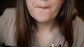 Stäng sig upp av den okända flickan i svarta handskar som äter en hamburgare i ett kafé arkivfilmer