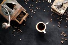 Stäng sig upp av den retro molar för gammal tappning med koppen av den bästa sikten för svart kaffe och för kaffebönor på svart b royaltyfria bilder