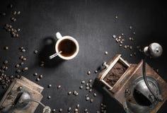 Stäng sig upp av den retro molar för gammal tappning med koppen av den bästa sikten för svart kaffe och för kaffebönor på svart b Royaltyfri Bild