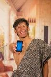 Stäng sig upp av den roliga förhistoriska mannen som ler till kameran och framme pekar hans mobiltelefon, i en suddig bakgrund Royaltyfri Bild