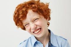 Stäng sig upp av den roliga röda haired pojken med fräknar som ler med stängda ögon och att göra enfaldiga framsidor, när modern  arkivfoton