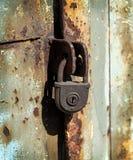 Stäng sig upp av den rostiga hänglåset på gammal metalldörr Arkivfoton