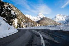 Stäng sig upp av den sceniska tomma vägen i bergpasserande i julian fjällängar i snöig vinterlandskap, Slovenien arkivbild